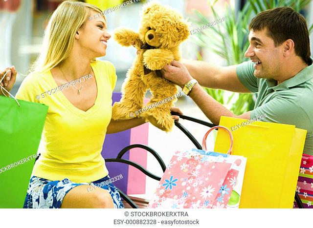 Portrait of happy man giving a teddy-bear to her girlfriend in the shop
