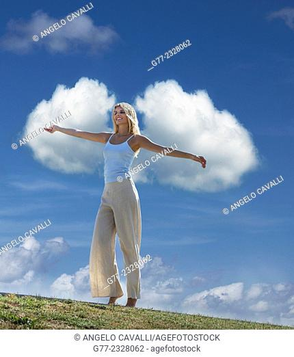 Young woman with open arms against clouds in the sky, Miami Beach, Florida, USA
