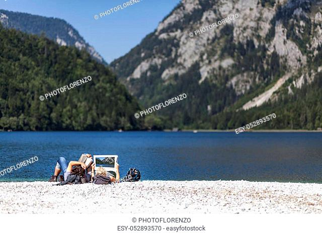 Couple reading book and newspaper on lake Leopoldsteiner near Eisenerz in Styria, Austria