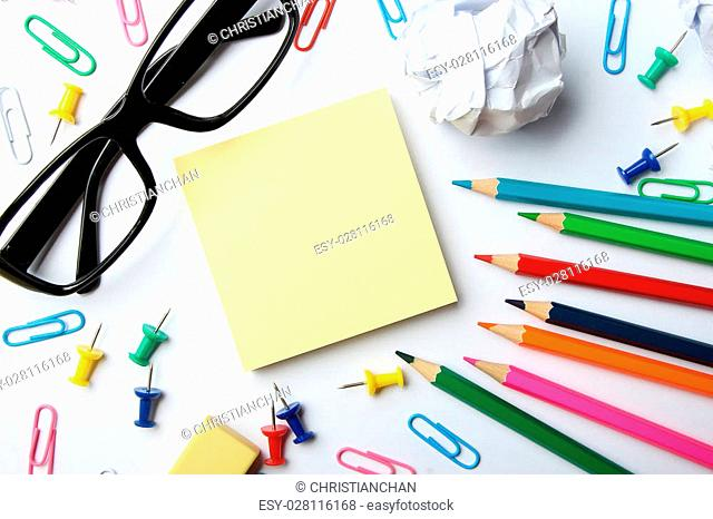 School supplies and blank sticky note block on the white paper background