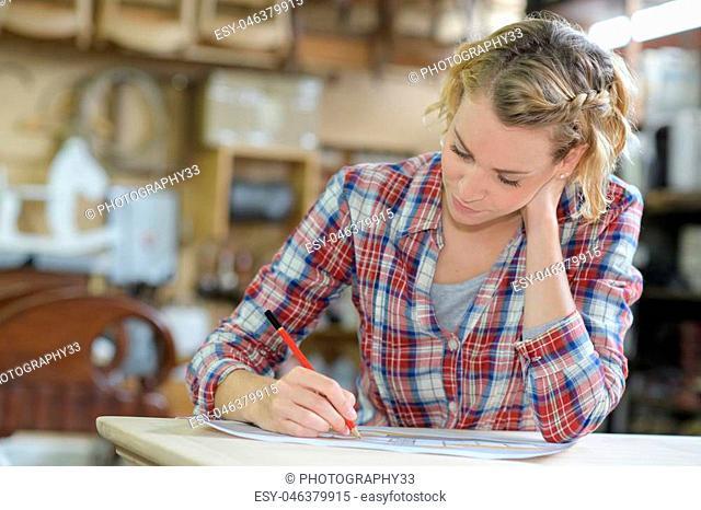 emale apprentice taking notes in workshop