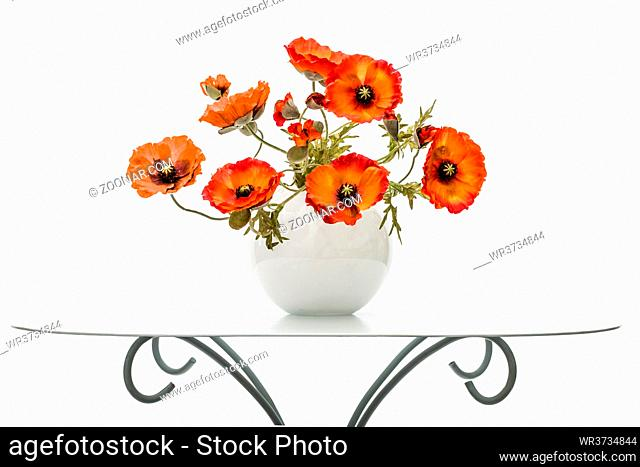 Vase with red poppies is on a coffee table, isolated on a white background