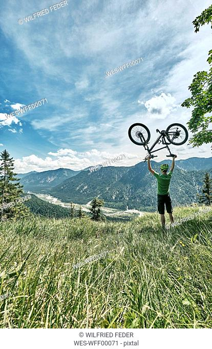 Germany, Bavaria, Isar Valley, Karwendel Mountains, mountainbiker on a trip lifting up his bike on alpine meadow