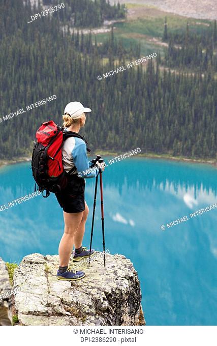 Female hiker on rock cliff overlooking blue alpine lake; British Columbia, Canada