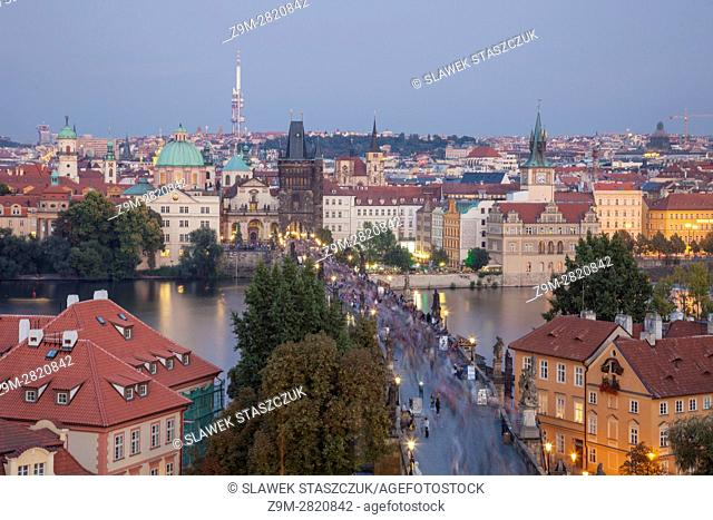 Dusk in Prague old town, Czech Republic. Crowd of tourists on Charles Bridge across Vltava river