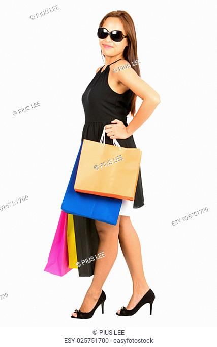 A full length portrait of confident Asian female shopper stands profile posing with arms akimbo wearing a stylish black dress with colorful department store...