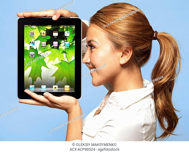 Smiling young woman looking at Apple iPad tablet in her hands isolated on blue background