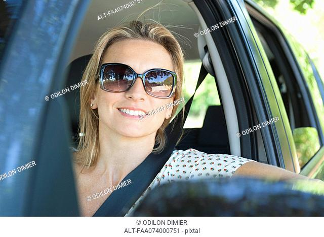 Woman in car, smiling out window, portrait