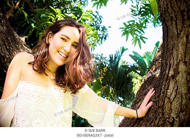 Portrait of teenage girl climbing tree