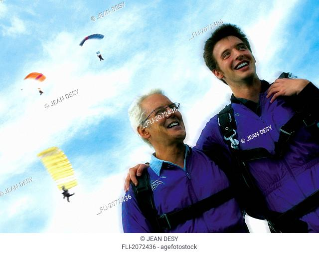 Father And Son Smiling, Three Parachutists Flying In Sky Background