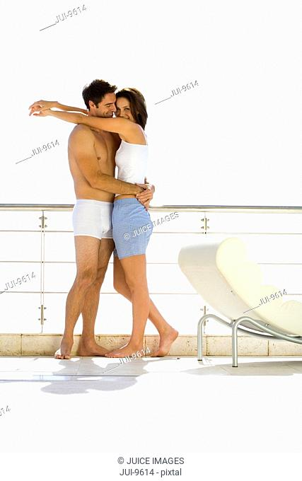 Young couple embracing on balcony, side view