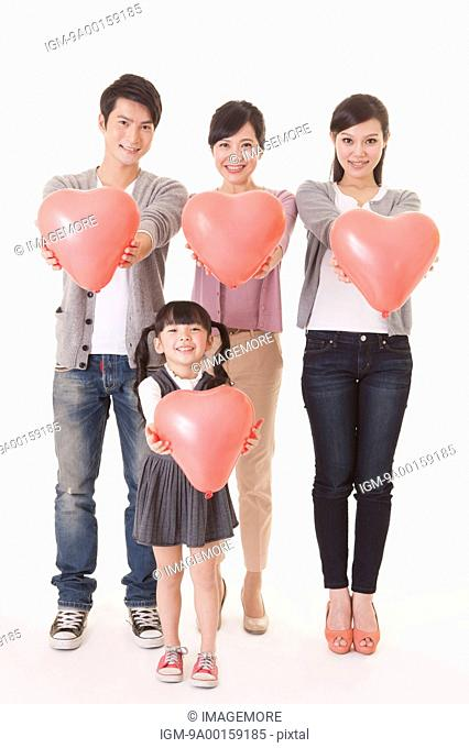 Three generation family standing and holding balloon with smile
