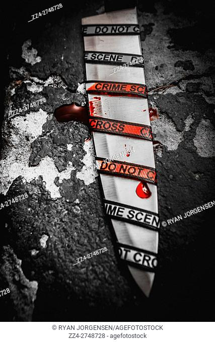 Red blood spills at the scene of a underworld crime hit with a knife blade under a investigation of cross examination