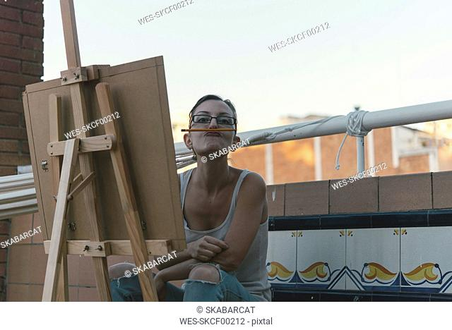 Young woman with easel making funny faces on roof terrace of her penthouse