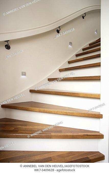 Modern steel staircase with wooden steps in a new apartment in a residential building with spots light in wall close-up