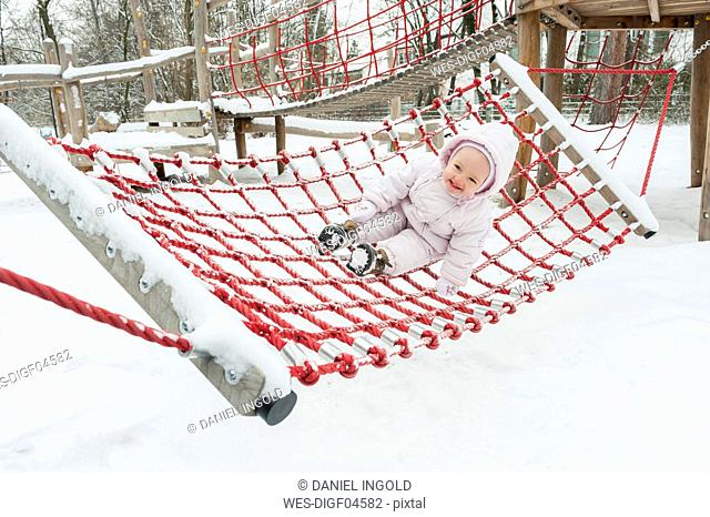 Baby girl having fun on swing in winter