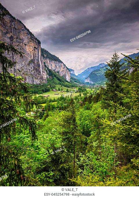 The Lauterbrunnen valley in cloudy rainy weather with high waterfalls in background, near Interlaken in the Bernese Oberland, Switzerland