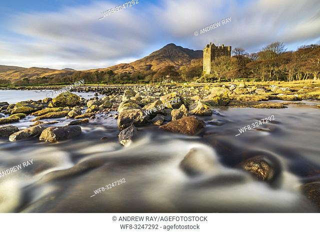 Moy Castle at the head of Loch Buie on the Isle of Mull illuminated by late afternoon sunlight. A long shutter speed was utilised to blur the movement in the...