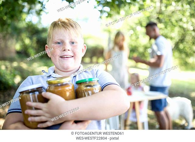 Portrait of boy holding jars outdoors with family in background