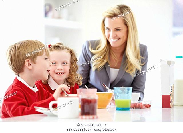 Mother And Children Having Breakfast In Kitchen Together