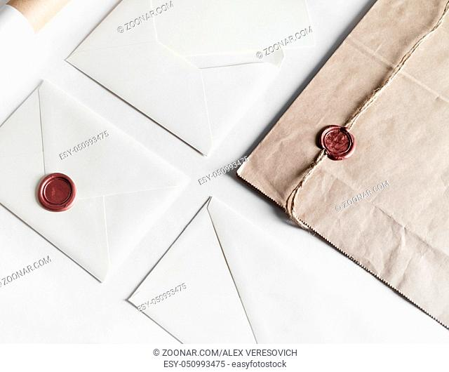 Envelopes and seal stamp on paper background. Vintage still life with postal accessories. Blank stationery. Responsive design mockup