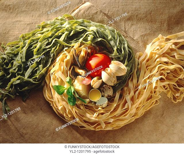 Top shot of green & Egg Tagliatelli with clams Tomato and garlic ingredients