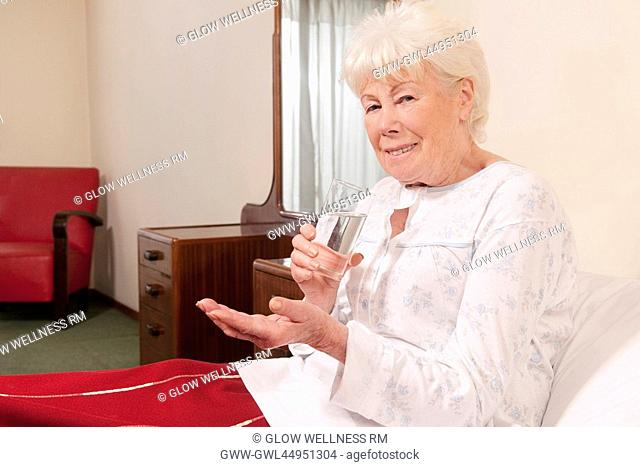 Woman sitting on the bed and taking medicine