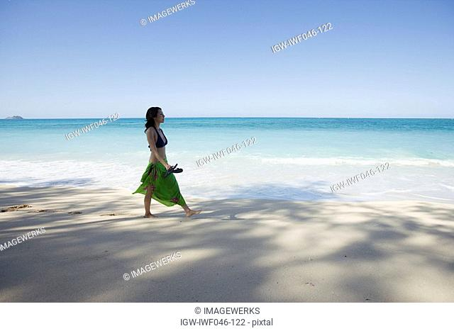 A young woman walking on beach
