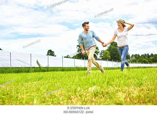 Young couple holding hands, running through field, next to solar farm