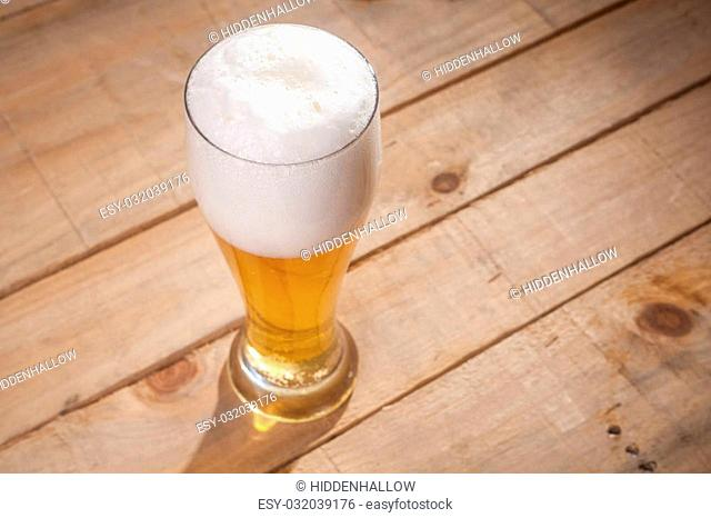 Tall glass full of light lager beer on a wooden table