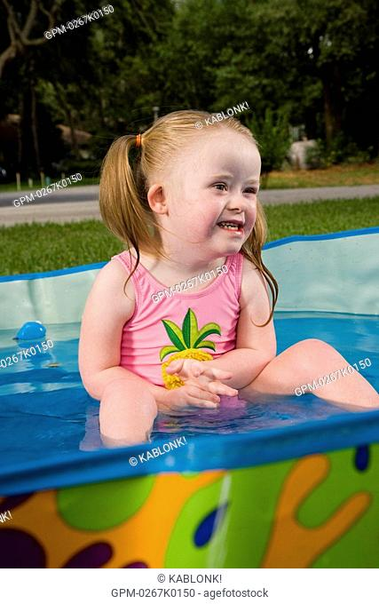 Side view of a girl with downs syndrome playing in kiddie pool