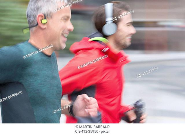 Smiling male runners with headphones running