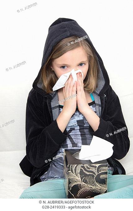 girl in a black hood, blowing her nose and sneezing