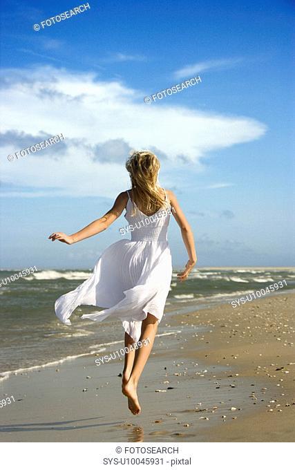 Caucasian pre-teen girl running down the beach in flowing white dress