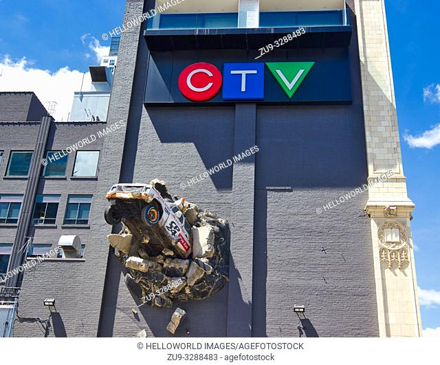 Sculpture of news truck breaking out of wall, CTV (City TV) building (1913), Queen Street West, Toronto, Ontario, Canada