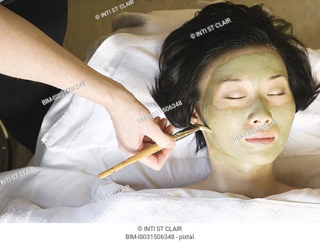 Asian woman receiving spa facial treatment