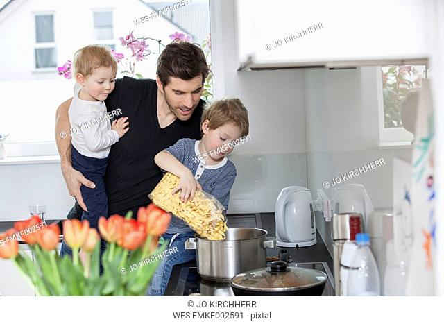 Father with baby on arm watching son preparing noodles