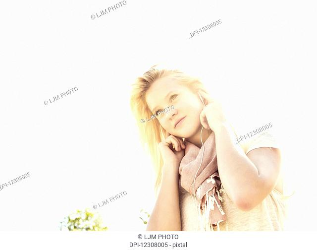 Beautiful young woman with long blond hair listening to music outdoors on her smart phone in a city park in autumn; Edmonton, Alberta, Canada