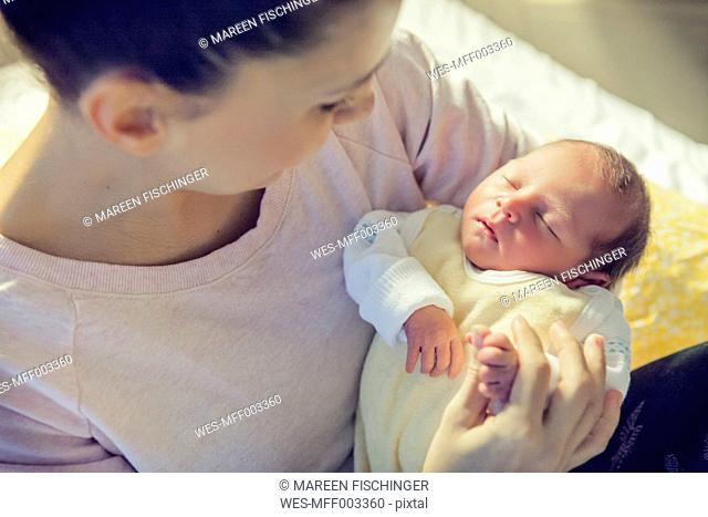 Mother holding her newborn baby in hospital bed