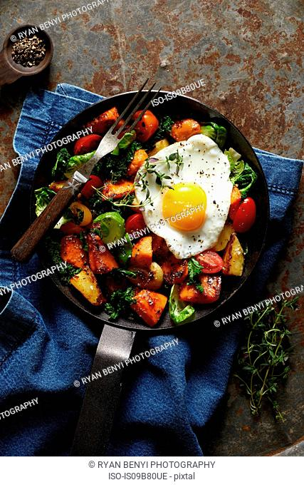 Breakfast hash with fried egg in cast iron skillet