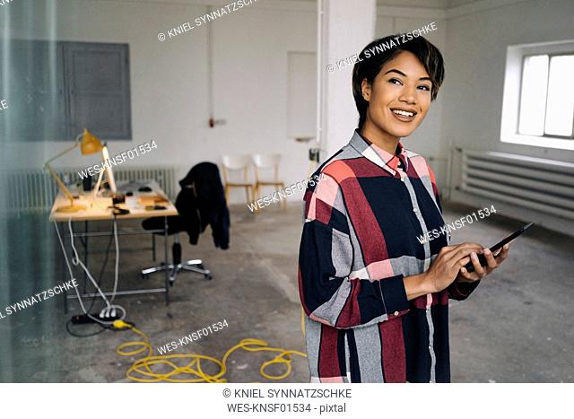 Smiling woman using tablet in empty office