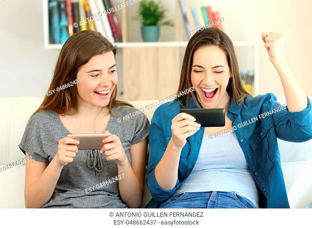 Front view portrait of two excited friends playing games and winning sitting on a couch in the living room at home