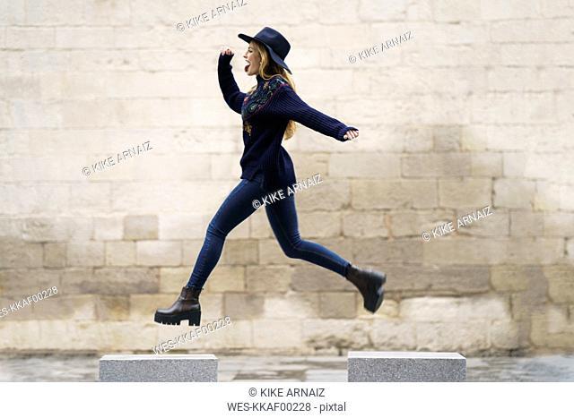 Young woman jumping from bollard to bollard