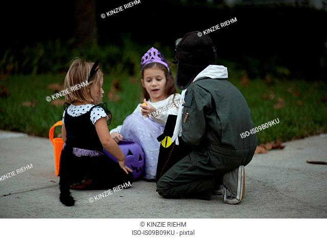 Boy and sisters trick or treating crouching and looking at treats on sidewalk
