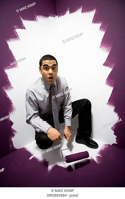 Portrait of a businessman painting himself into a corner