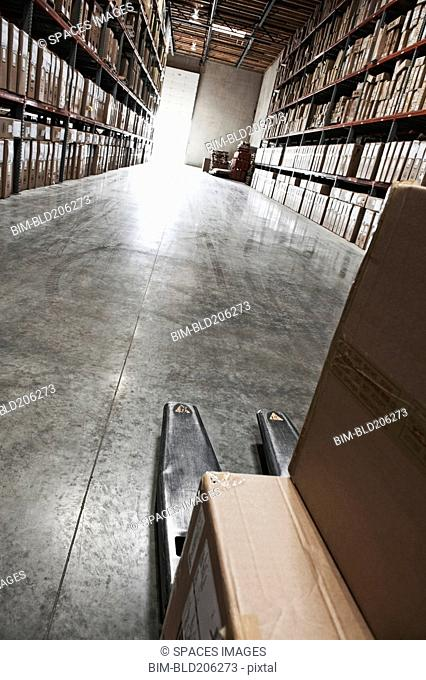 Cardboard boxes on forklift in warehouse