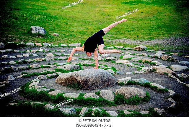 Acrobat performing on stone arrangement, Bainbridge, Washington, USA