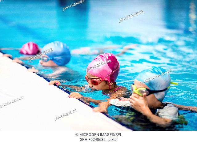 Group of children in swimming class, making bubbles