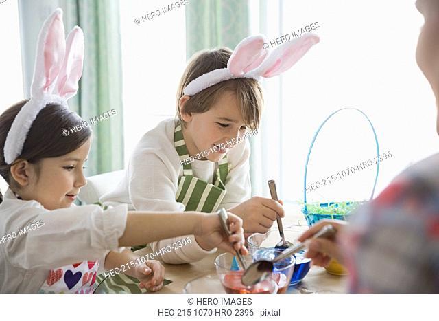 Siblings coloring Easter eggs