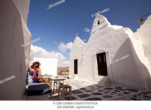 Woman sitting at a open-air cafe near Paraportiani Church, Mykonos, Cyclades Islands, Greek Islands, Greece, Europe
